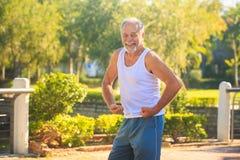 Grey Old Man en los brazos Musculars de las tensiones del chaleco sonríe en parque foto de archivo libre de regalías
