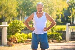 Grey Old Man en los brazos Musculars de las tensiones del chaleco sonríe en parque fotos de archivo