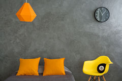 Grey and orange room. Bedroom with grey walls and bed and colorful additions. Orange pillows, lamp and yellow chair in grey dark room Royalty Free Stock Photography