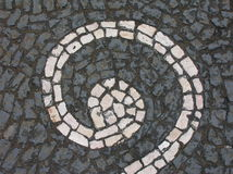Grey paving with white spiral. Gray rough textured cobblestones with a decorative painted white spiral in Portugal Stock Photo