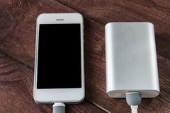 Grey phone and power bank connected by cord Stock Image