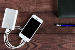 Grey phone and power bank connected by cord with pen and noteboo Stock Photo