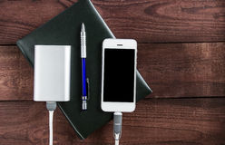 Grey phone and power bank connected by cord with pen and noteboo Stock Photos