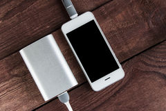Grey phone and power bank connected by cord on wooden desk Royalty Free Stock Photos