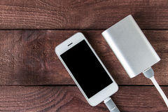 Grey phone and power bank connected by cord on wooden planks Royalty Free Stock Photos