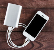 Grey phone and power bank connected by cord on wooden table Royalty Free Stock Image