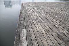 Grey pier and reflection of buildings on river picture stock image