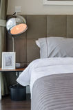Grey pillow on bed with lamp Stock Photography