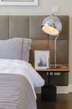 Grey pillow on bed with modern lamp Royalty Free Stock Photo