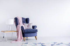 Grey pillow on blue armchair. Grey pillow and pink blanket on dark blue armchair next to table with lamp in white room with geometric carpet Stock Images