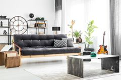 Guy`s living room design. Grey pillow on dark settee and round clock on the wall in guy`s living room interior design with guitar and metal and wooden furniture Stock Photography