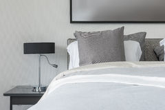 Grey pillow on white bed in modern bedroom with black lamp Stock Images