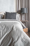 Grey pillow on white bed in modern bedroom with black lamp Stock Photography