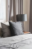 Grey pillow on white bed in modern bedroom with black lamp Stock Photos
