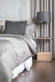 Grey pillow on white bed in modern bedroom with black lamp Royalty Free Stock Images