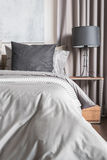 Grey pillow on white bed in modern bedroom with black lamp Royalty Free Stock Photography