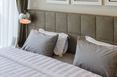 Grey pillows on bed with modern lamp Stock Image