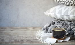 Grey pillows and cup of coffee on the wall background Royalty Free Stock Images