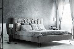 Grey pillows on king-size bed. And glass lamp on black nightstand in grey bedroom with decorative curtains Royalty Free Stock Images