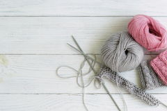 Grey and pink knitting wool and knitting needles on white wooden background. top view.copy space Stock Image