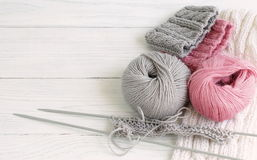 Grey and pink knitting wool and knitting needles on white wooden background. top view.copy space Stock Photos
