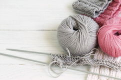 Grey and pink knitting wool and knitting needles on white wooden background. top view.copy space Royalty Free Stock Photography