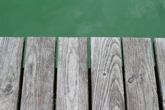 Grey plank over green water Stock Images