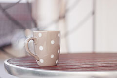 Grey polka dot cup on the round wooden table Stock Photo
