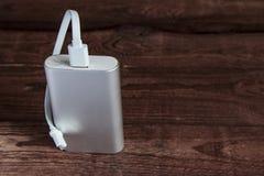 Grey Portable External Battery Powerbank på en trätabell royaltyfri fotografi