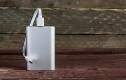 Grey Portable External Battery Powerbank på ett träskrivbord fotografering för bildbyråer