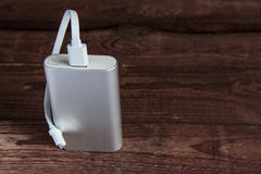 Grey Portable External Battery Powerbank sur un Tableau en bois Photographie stock libre de droits