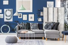 Grey pouf in living room. Grey pouf next to white and copper table in living room with grey couch set and gallery on blue wall Royalty Free Stock Photos