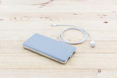 Grey powerbank and USB cable for smartphone. Stock Photos