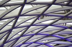 Grey and purple pipes forming an abstract pattern. Metal piping used for the construction of a building forming an abstract pattern. The lighting has turned the Stock Photo
