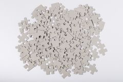 Grey Puzzles On White Background Top View. Heap Of Jigsaw Puzzles Grey Color On White Paper Background Top View. Assembly Of Puzzles. Developing Game Royalty Free Stock Image