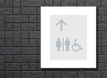 Grey restroom sign on black wall Royalty Free Stock Photos