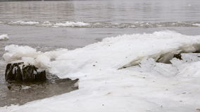 Grey river with a big block of ice. And bits of snow stock video