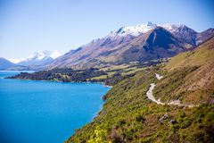 Grey Road Near Mountain Near Body of Water Photo Royalty Free Stock Images