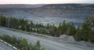 Grey road with person riding bicycle at deep mining quarry
