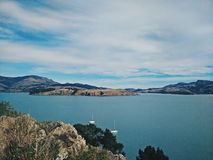 Grey Rock Cliff Overlooking Body of Water With Mountains in Distance Stock Images