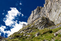 Grey rock, mountains on daytime with green grass against bright. Blue sky with white clouds going up, background, Spain, Picos de Europa. Perfect for extreme Stock Images