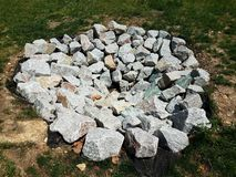 Grey rocks or stones or boulders in circular formation on grass royalty free stock photography