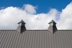 Grey Roof Vents mit blauem Himmel und geschwollenen Wolken Stockbilder