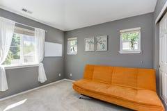 Grey room interior with bright orange sofa. Stock Photos