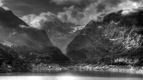 Grey Scale Photo of Body of Water Near Mountain Ranges Royalty Free Stock Images