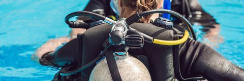 Grey scuba diving air oxygen tank on the back of a scuba diver BANNER, long format. Grey scuba diving air oxygen tank on the back of a scuba diver. BANNER, long royalty free stock photo
