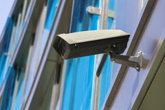 Grey security camera attached to wall with blue windows in background Stock Photos