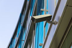 Grey security camera attached to wall with blue windows in background Stock Images