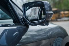 Modern car side mirrors with indicator built in honda lane watch camera. Grey sedan foldable side mirror external with built in indicator slit and camera for Stock Photo