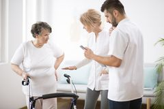 Grey senior lady with walker during physiotherapy with professional female doctor and male nurse royalty free stock photo